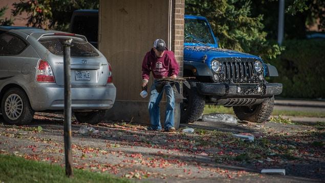 Un homme qui ramasse des débris dans le secteur Mont-Bleu.