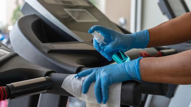 Une employée, les mains protégées par des gants bleus, applique du désinfectant sur les poignées d'une machine d'exercice dans une salle de sport.