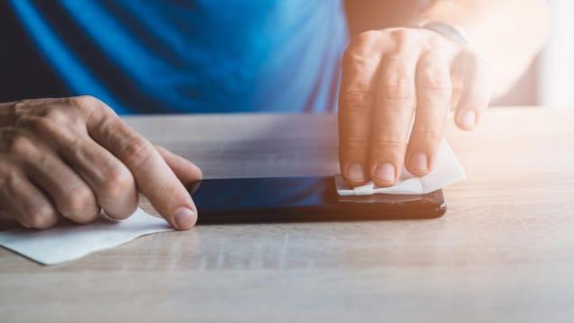 Une homme nettoie l'écran d'un téléphone intelligent avec une lingette.