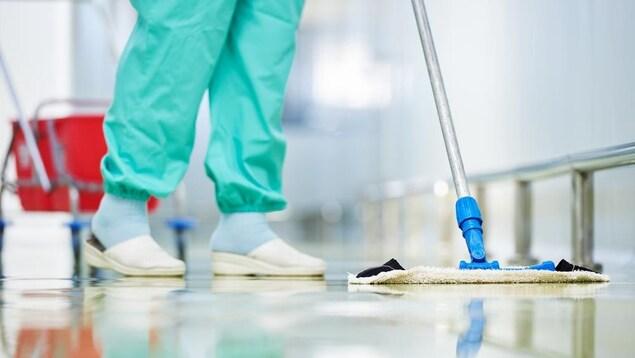 Une personne lave un plancher.