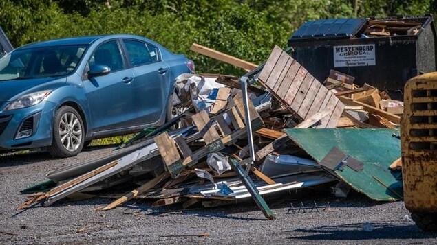 Un tas de débris jonchent le sol devant un conteneur à déchets plein.