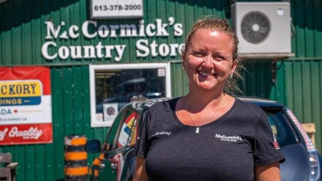 Une femme devant le McCormick's Country Store à Camden East.
