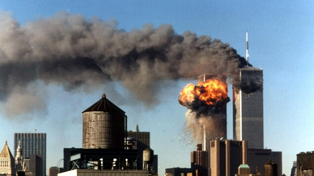 Une boule de feu s'échappe de la tour sud du World Trade Center, à New York, le 11septembre 2001. Le vol 175 de United Airlines a percuté la tour à 9 h 03, heure de l'Est, soit un peu plus de 15 minutes après que le vol 11 d'American Airlines a percuté la tour nord, de laquelle s'échappe toujours un panache de fumée.