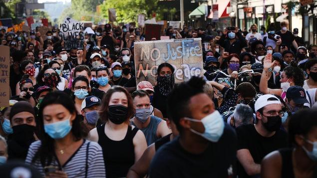 Une foule compacte marche dans une rue.