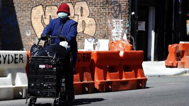 Une femme pousse un chariot de courses et porte un masque de protection.
