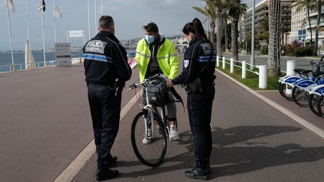 L'homme montre ses papiers aux policiers.