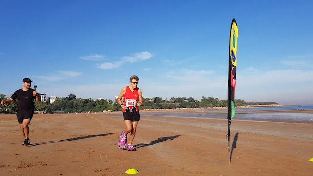 Nick Ackers court sur une plage avec ses raquettes à sable.