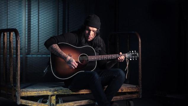 Un homme joue de la guitare.