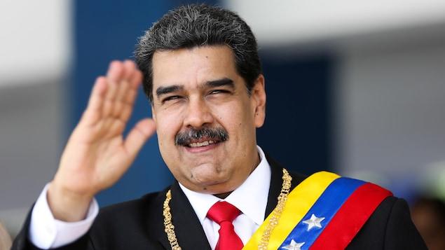 Nicolas Maduro portant une écharpe et un collier et saluant de la main droite