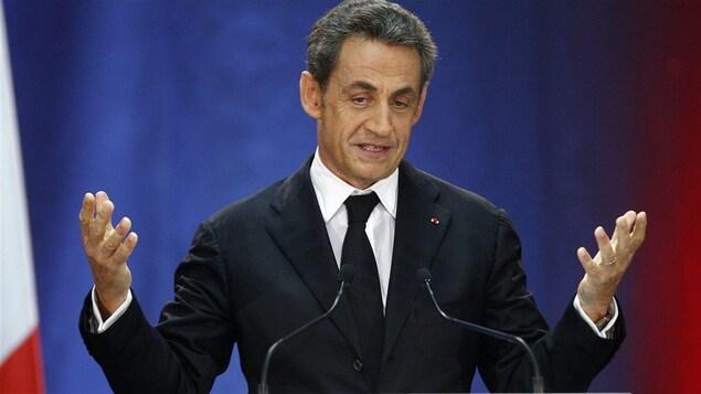 Nicolas Sarkozy debout derrière un pupitre et des micros, les avant-bras levés.