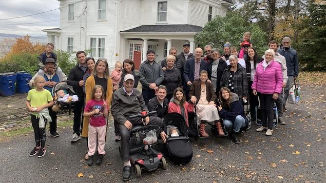Nicole Guertin entourée d'une vingtaine de membres de sa famille devant une maison.