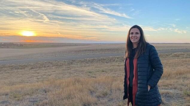 Nicole se tient debout dans un champ, en automne, au bord de la route et avec un coucher de soleil à l'horizon.