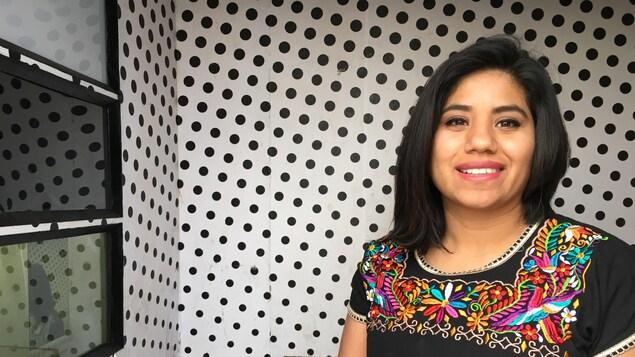 Nidia Romero se tient dans la cabine-photo itinérante.