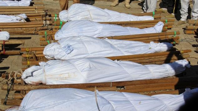 De nombreux corps sont enveloppés dans un drap blanc et déposés sur une civière de bois au sol.