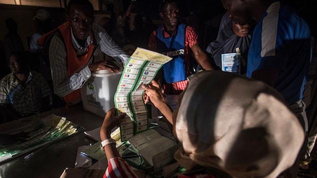 Une femme regarde un bulletin de votes alors que d'autres personnes s'affairent autour d'elle dans une pièce plongée dans la pénombre.