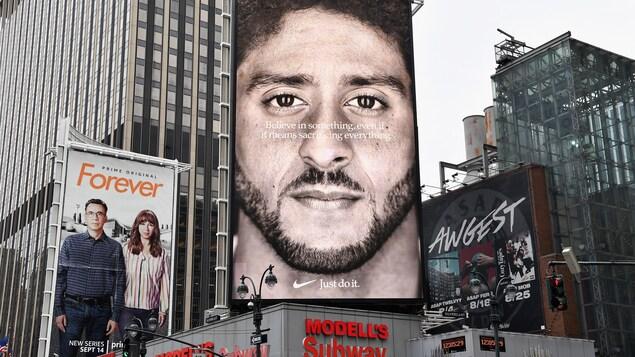 Au centre, l'ancien quart-arrière des 49ers de San Francisco, Colin Kaepernick, est sur une affiche où on peut lire « crois en quelque chose, même si cela veut dire tout sacrifier ».