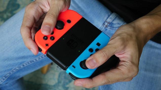 Une personne joue avec une manette de Nintendo Switch.