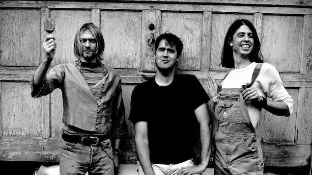 Les trois musiciens posent devant une voiture dans un garage.