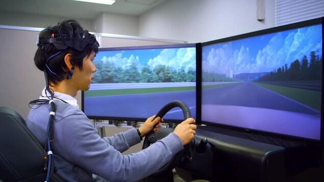 Une photo montrant un jeune homme asiatique équippé d'un casque branché à plusieurs fils en train de conduire dans un simulateur.