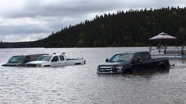 Des camions inondés par la montée du niveau de l'eau d'un lac de l'Abitibi.
