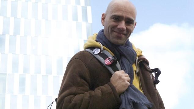 L'humoriste Karim Slama est photographié, souriant, en contre-plongée devant le siège de la RTS.