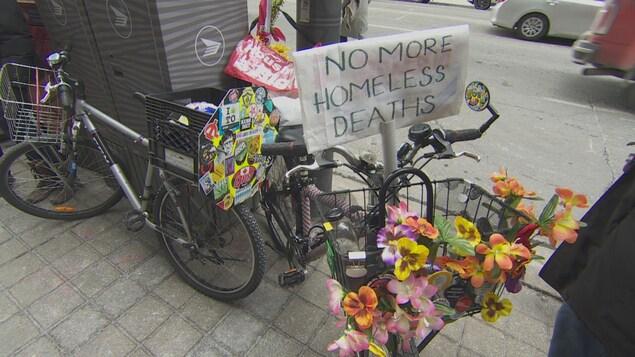 Des vélos portent des fleurs et des panneaux protestant contre l'insécurité des sans-abris.