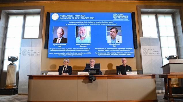 Le comité siège devant un écran où apparaissent les portraits des trois lauréats.三位科学家 Syukuro Manabe, Klaus Hasselmann 和 Giorgio Parisi 获得 2021 年物理学诺贝尔奖。