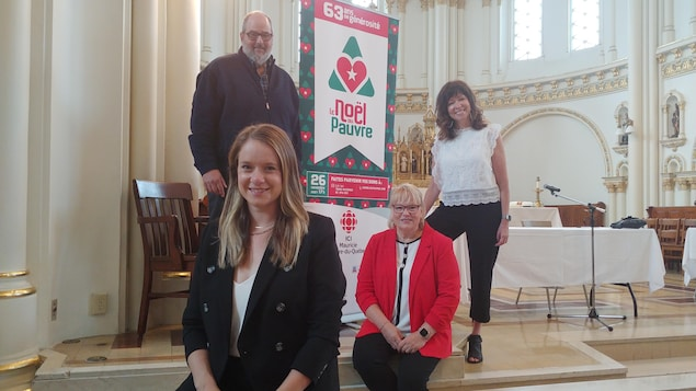 Un homme et trois femmes posent devant une pancarte du Noël du pauvre.