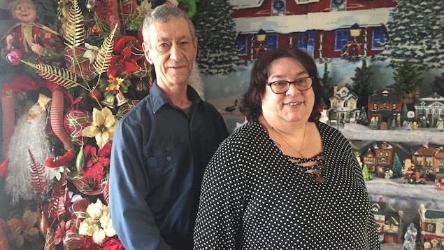 Un homme et une femme se tiennent debout devant un arbre de Noël et plusieurs décorations de Noël.