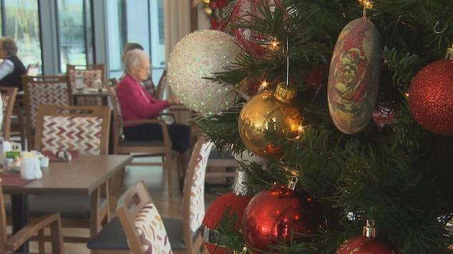 Un sapin de Noël dans une salle à manger où se trouvent des aînés.