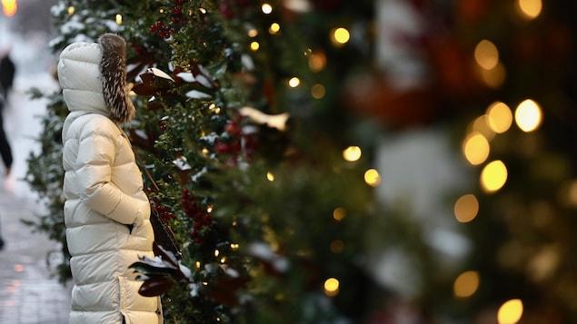 Une femme qui porte un manteau d'hiver regarde des arbres décorés pour Noël.