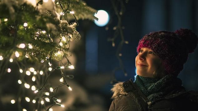 Une jeune fille regarde un sapin illuminé en souriant.