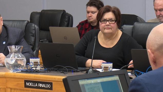 Noella Rinaldo écoute un présentateur lors d'une réunion du conseil municipal.