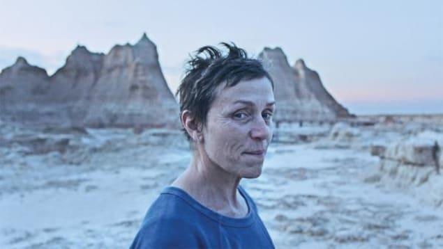 Une femme regarde vers l'objectif dans un désert, avec des montagnes en arrière-plan.