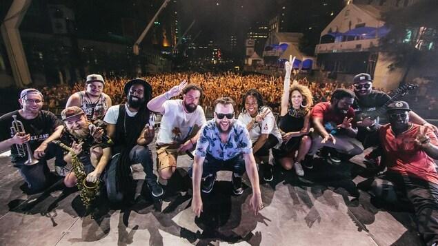 Le groupe Nomadic Massive prend fièrement la pose sur la grande scène du Festival de jazz de Montréal, avec la foule en arrière-plan.