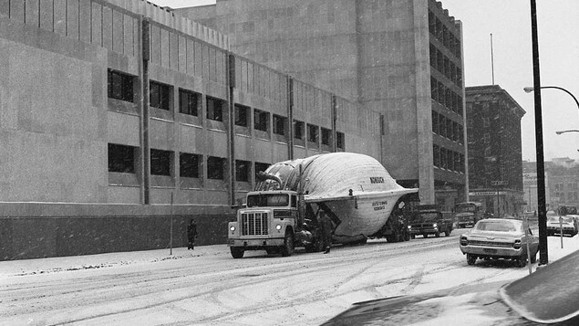 Un camion transporte un bateau dans une rue du centre-ville de Winnipeg.