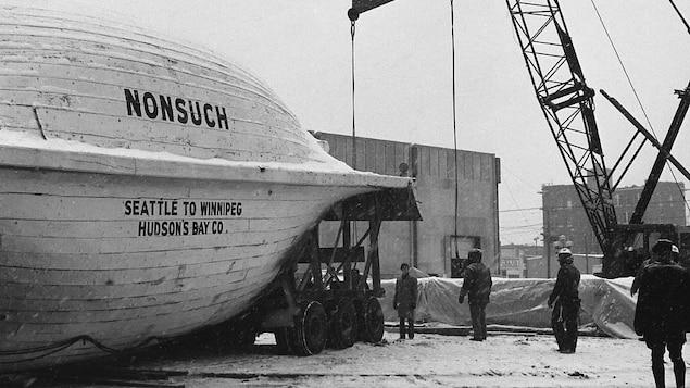 Un bateau déposé sur le sol. Il gît sur le flanc et on peut voir son nom inscrit sur la coque. Autour : une grue et des hommes au travail.
