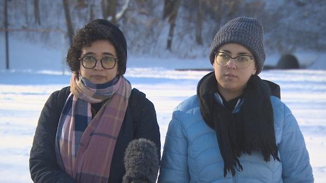 Deux femmes vêtues de manteaux, de tuques et de foulards dans un parc