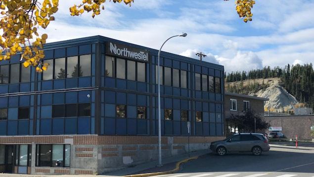 Le bâtiment de deux étages de Northwestel à Whitehorse avec une voiture garée devant et des arbres aux feuilles automnales.