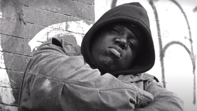 Notorious B.I.G. affiche un air boudeur en croisant les bras devant un mur de briques.