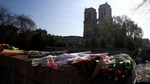 Des bouquets de fleurs ont été déposés sur un pont non loin de la cathédrale. On peut voir Notre-Dame de Paris au loin.