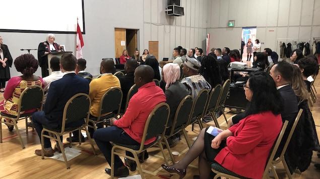 أشخاص جالسون في قاعة في مونكتون خلال مراسم منح الجنسية الكندية لـ48 مقيماً دائماً.