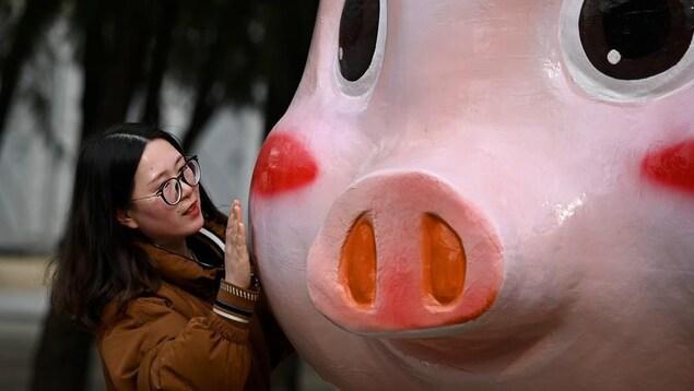 Un femme touche la joue d'une figurine de cochon