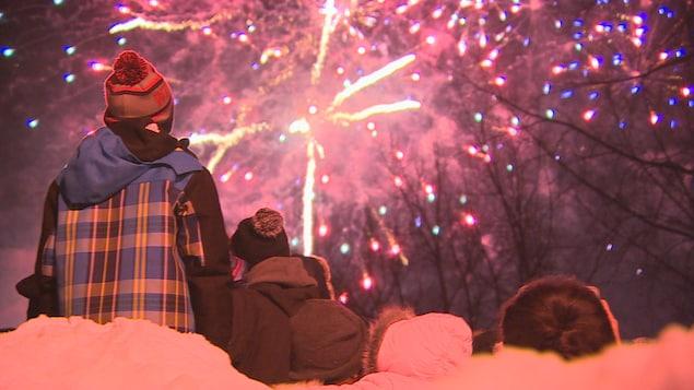 Des gens de dos regardent un feu d'artifice, en hiver.