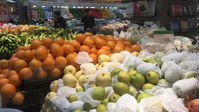 Des fruits frais dans des étalages d'épicerie: des pommes, des poires, des oranges, des bananes.