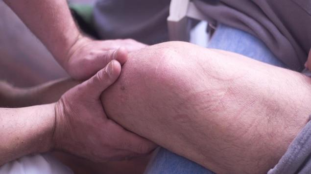 Image anonyme. Un homme reçoit un traitement à un genou