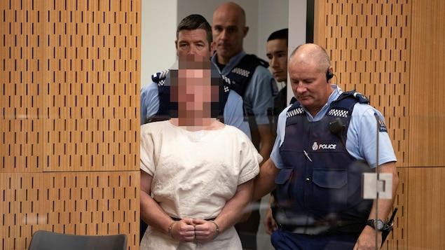 Un accusé vêtu d'une tunique est accompagné par des policiers.