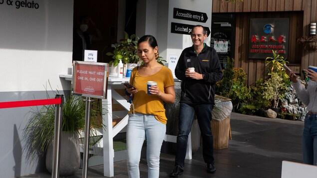 Une femme et un homme souriant marche, café en main.