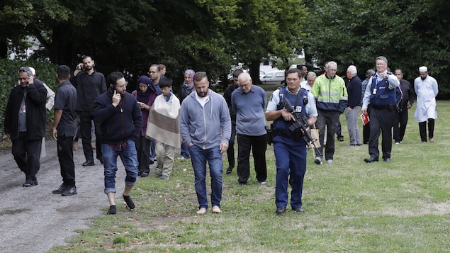 Une foule est escortée par des policiers.