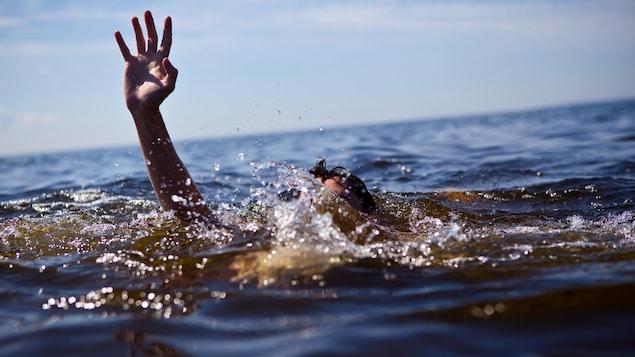 Une personne qui se noie tend la main pour être secourue.